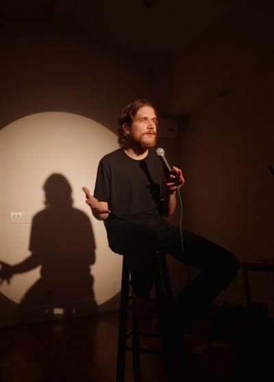 Bo Burnham, sitting on a stool flexing his comedy skills